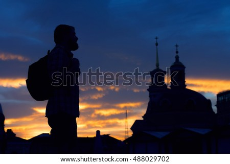 Silhouette of man on sky background sunset and the church. Pilgrimage to holy places.