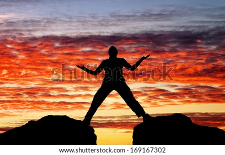Silhouette of man on sunset fiery sky background  - stock photo