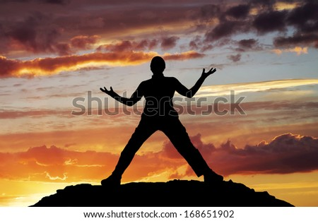 Silhouette of man on sunset sky background  - stock photo