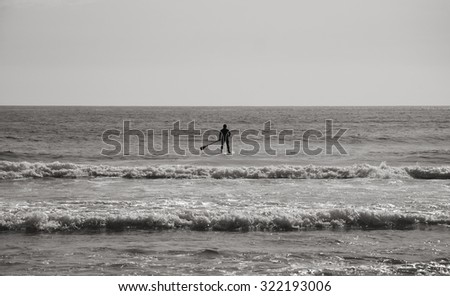 Silhouette of man paddleboarding in the ocean. Man and nature concept. Black and white.