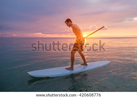 Silhouette of man paddling on paddle board at sunset. Water sport near the beach on sunset - stock photo