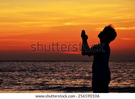silhouette of man praying during sunset - stock photo