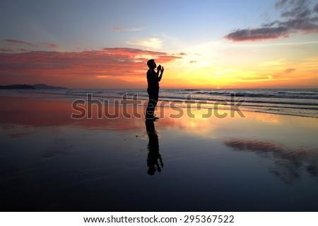 silhouette of man praying during sunset. - stock photo