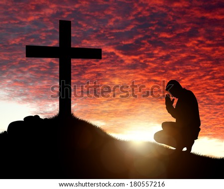 Silhouette of man praying to a cross with heavenly cloudscape sunset concept for religion, worship, love and spirituality - stock photo