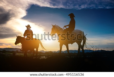 Silhouette of man riding a horse on sunset with beautiful background.Three cowboys silhouetted against a dawn sky. Montana horse ranch