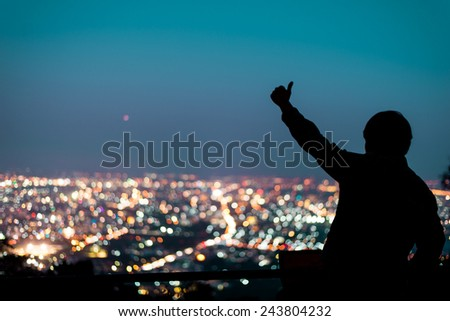 Silhouette of man showing thumb up above the city in the night - stock photo