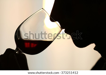 Silhouette of man sniffing red wine in a glass, close up