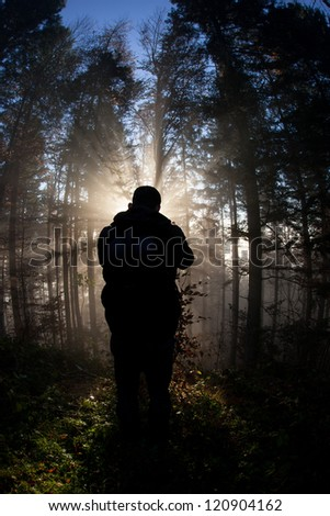 silhouette of man standing in sunbeams in forest - stock photo