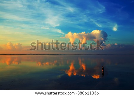 Silhouette of  man standing on water with reflection of amazing sunset cloud. - stock photo