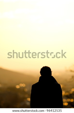 silhouette of man standing over freiburg in sunset