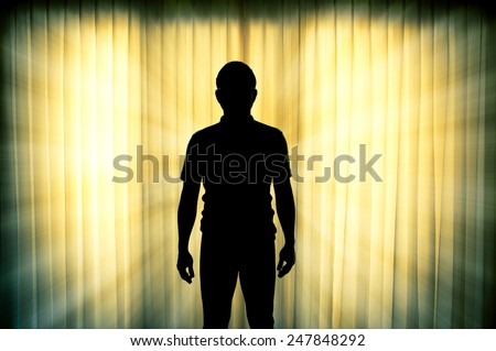 Silhouette of man standing with light ray effect background - stock photo