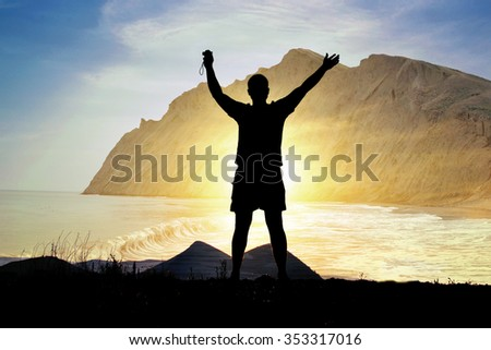 Silhouette of man tourist with arms raised with a camera on a mountain slope on the background of  mountains, sea and sun (double exposure)