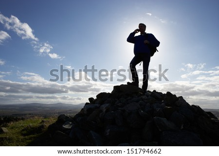 Silhouette Of Man Using Mobile Phone In Remote Countryside - stock photo