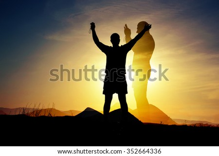 Silhouette of man with arms raised on a mountain slope on the background of  mountains, sea and sun (double exposure)