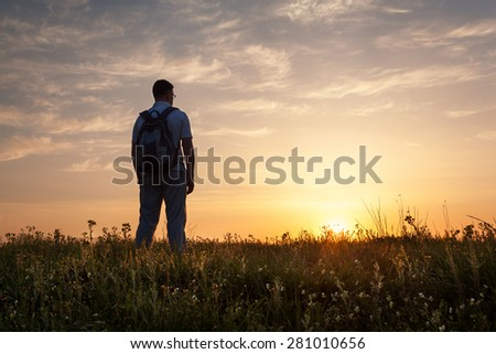 Silhouette of man with arms raised up and beautiful sky. Element of design. Summer sunset. Background - stock photo