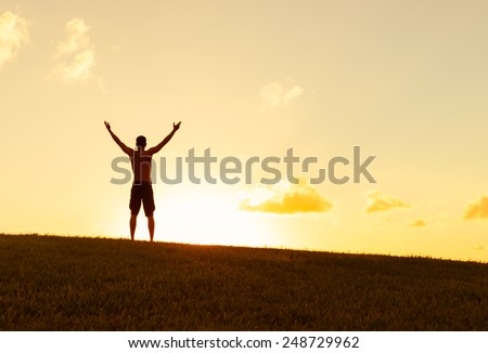 Silhouette of man with hands raised into sunset - stock photo