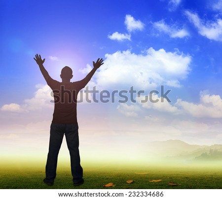 Silhouette of man with hands raised to beautiful autumn sunset background. A disabled man standing up. Positive concept of cure, recovery, medical miracle, hope, insurance etc. Hallelujah concept. - stock photo