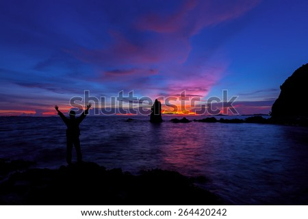 Silhouette of Man with hands raised to beautiful sunset  - stock photo