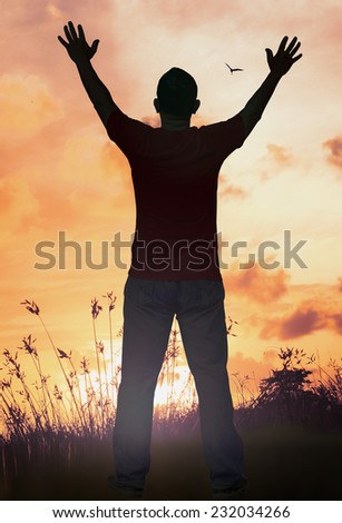 Silhouette of man with hands raised to beautiful sunset background. Worship Forgiveness Mercy Humble Evangelical Hallelujah Thankful Praise Redeemer Amen Pray concept. - stock photo