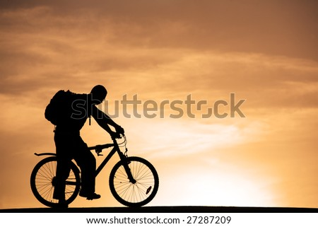 Silhouette of man with knapsack at mountain bicycle at sunset