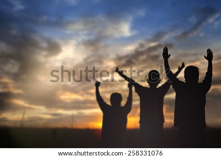 Silhouette of man with raised hands over blur nature background concept for religion, worship, prayer and praise.