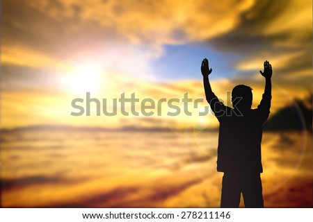 Silhouette of man with raised hands over blur sea concept for religion, worship, prayer and praise. - stock photo