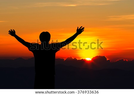 Silhouette of man with raised hands over sunset background.