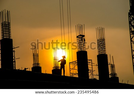 silhouette of man working for building - stock photo