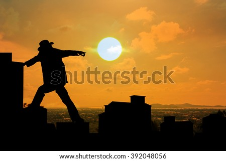 silhouette of man working on buildings pointing at sunset
