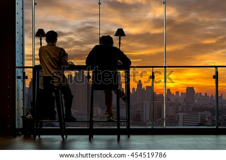 Silhouette of Man works at the workplace beside the windows with the cityscape building background, business workplace concept