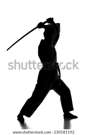 Silhouette of martial arts man is standing with a sword, isolated on the white background.