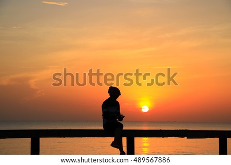 Silhouette of men  in the morning at the beach waiting for the sunrise