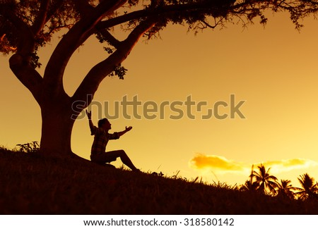 Silhouette of men with hands raised into the sunset. - stock photo