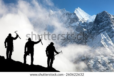 Silhouette of men with ice axe in hand and mountains with clouds - Mount Thamserku and Mount Kangtega - Nepal - stock photo
