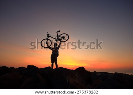 Silhouette of mighty man in action lifting bike above his head on rock mountain with sunrise twilight background. Symbol of relax, success and touring.