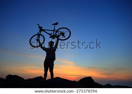 Silhouette of mighty man in action lifting bike above his head on rock mountain with sunrise twilight background. Symbol of relax, success and touring. - stock photo