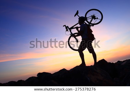 Silhouette of mighty man in action lifting bike on his shoulder on rock mountain with sunrise twilight background. Symbol of relax, success and touring.