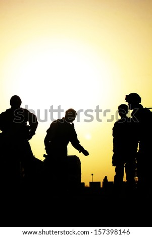 Silhouette of military mission planning against a sunset - stock photo