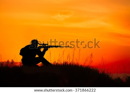 Silhouette of military sniper with sniper gun at sunset. shot, holding gun, colorful sky, background - stock photo