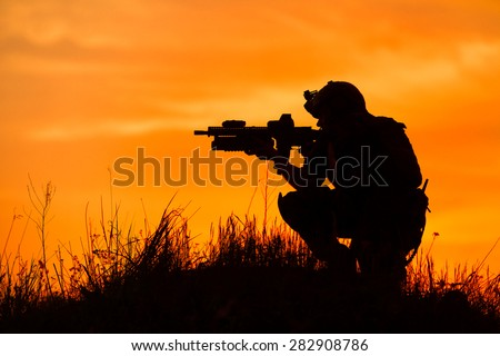 Silhouette of military soldier or officer with weapons at sunset. shot, holding gun, colorful sky, background - stock photo