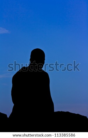 Silhouette of monk meditating at the top of the mountain - stock photo