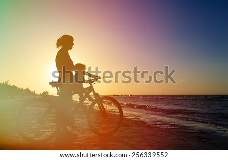 Silhouette of mother and baby biking at sunset sea