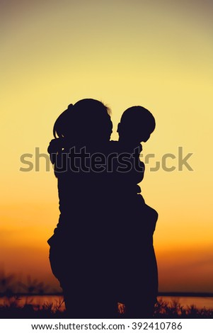 Silhouette of mother and child enjoying the view at riverside. Mother hugging her son on colorful sunset sky background. Friendly family. - stock photo