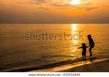 silhouette of mother and daughter play jumping on sand beach in the morning - stock photo