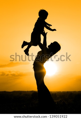Silhouette of mother playing with her son backlit by sunset - stock photo