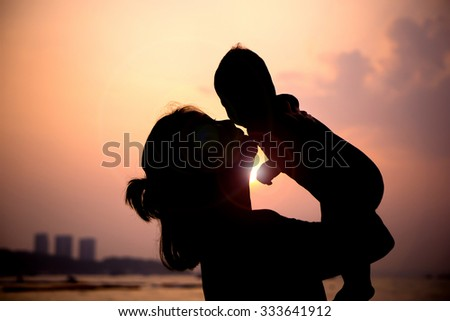 Silhouette of mother  with her toddler against the sunset and lens flare - stock photo