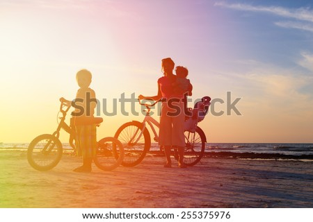 silhouette of mother with kids biking at sunset