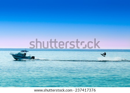 silhouette of motor boat and wakeboarder jumping crazy trick   - stock photo