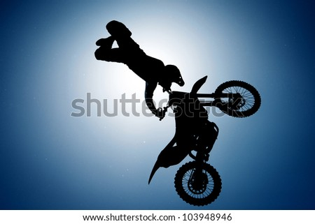 Silhouette of motorcycle rider performing trick - stock photo