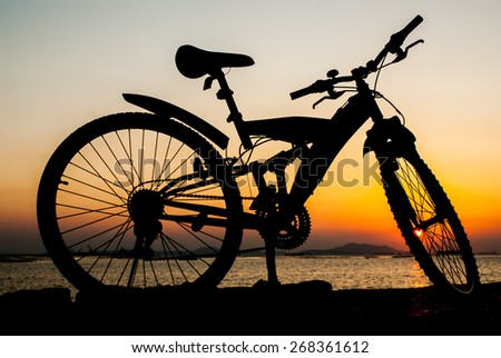 Silhouette of mountain bike parking on jetty beside sea with sunset sky background - stock photo